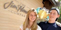 A Muppet peers over the shoulders of a young couple outside The Jim Henson Company