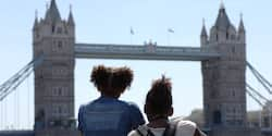 The backs of 2 kids who are looking at London Bridge in London, England