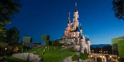 Sleeping Beauty Castle at Disneyland Paris is lit up against the nighttime sky