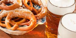 A plate of salted german pretzels sits next to 2 steins of beer