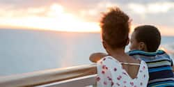 2 people look out at the sun setting into the sea from the ship's railing