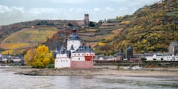 A small village is nestled between a river and the base of a lush hill with a castle
