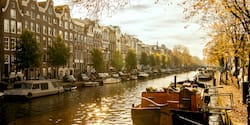 Boats anchored on bothe sides of a building-lined canal in Amsterdam