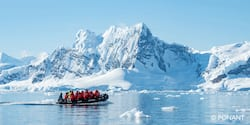 Group of parka clad Adventurers in a Zodiac boat navigating a strait to reach the snowy Antarctica shore