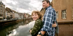 A boy, his father, and the rest of the family look out over a river in a European city