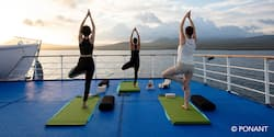 The backs of three women doing yoga on the deck of a ship while looking out over the water