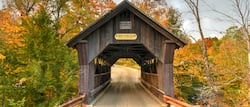 A head-on view of a wooden covered bridge with a sign that reads 'No Trucks or Buses Allowed' on a road surrounded by trees
