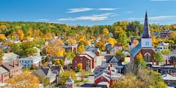The town of Montpelier, Vermont featuring a church with a large steeple and a large grove of trees