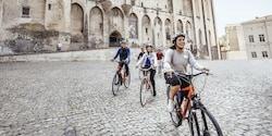 Five people ride bikes on a cobblestone street