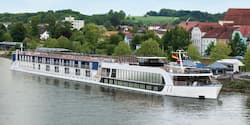 A modern ferry flying the German flag stops at a port in front of green, rolling hills