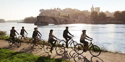 An Adventure Guide leads a group of helmet-clad bicyclists on a path along the bank of the Rhône River across from Lyon, France