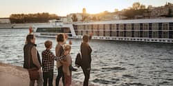 A family of five on land waves to a passing AmaWaterways ship