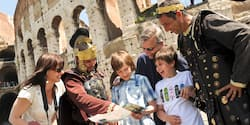 Tourists consult a map with men dressed in emperor and soldier costumes near the Roman Colosseum