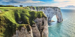 Grass covered cliffs with an arch-shaped structure rise high above the water
