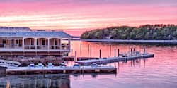 A house on the water in Bar Harbor, Main sits across the lake from a forest-lined river bank at sunset