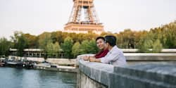 Two men with their arms resting on a wall near the Eiffel Tower