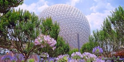 Spaceship Earth at Epcot in Walt Disney World Resort is framed by a foreground of flowers and trees
