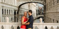 A smiling couple embracing on a pedestrian bridge in Venice