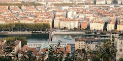 A river boat ship sails through the city of Lyon, France near a bridge along the Rhône River