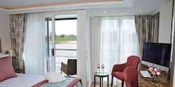 A Category AA room, featuring a double bed, two club chairs and a sliding balcony door leading to an outdoor seating area.