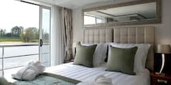 A Category AB room, featuring a double bed and a sliding balcony door.