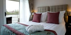 A Category BB room, featuring a double bed and a table with chairs, outside of a sliding balcony door.