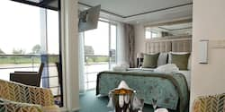 A Category Suite room, featuring a double bed, club chairs and a sliding balcony door leading to an outdoor seating area.