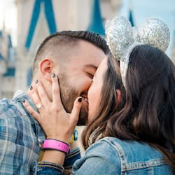 A couple kisses in front of Cinderella Castle
