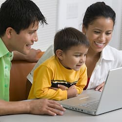 A smiling mother, father and young son looking at a laptop computer's screen