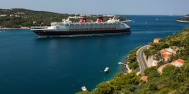 The Disney Magic cruise ship sails through an inlet between the shorelines of Dubrovnik, Croatia