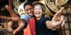 A teenage boy and an older woman smile as they extend their arms and give the peace sign with their hands while standing in front of a display of straw hats.