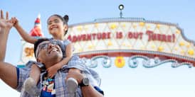 "A smiling girl holds her father's hand while on his shoulders in front of a sign that reads ""Adventure Is Out There!"""