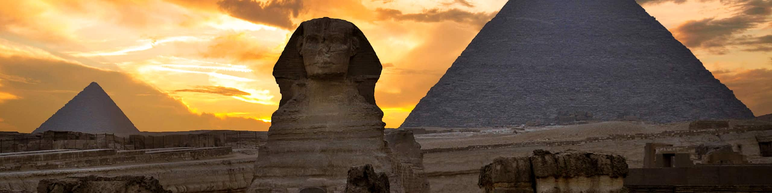 The Sphinx sits between 2 pyramids at sunset beneath a cloudy sky