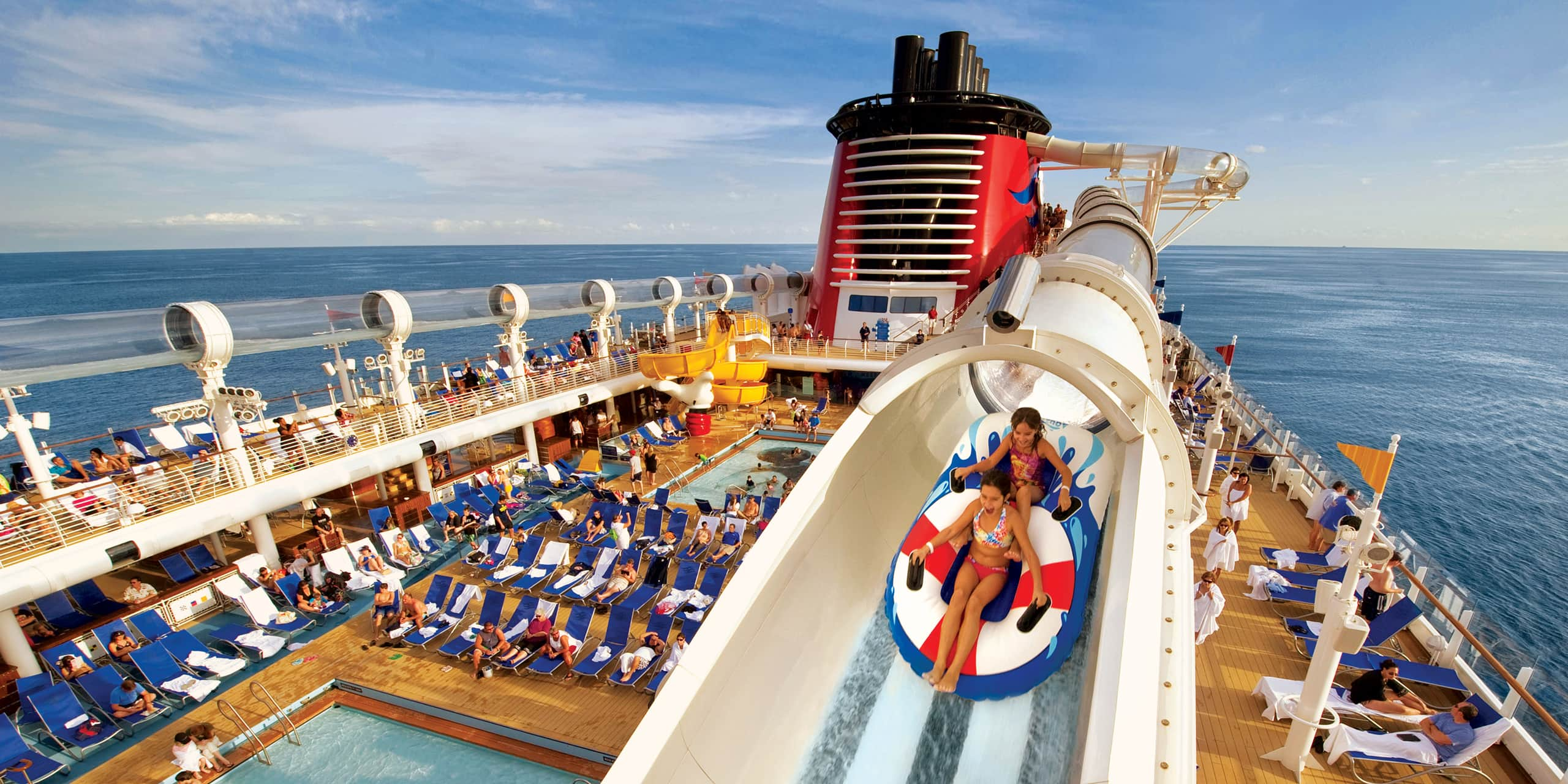 Two girls on inflatable rafts propelling through the AquaDuck waterslide above a pool area on a Disney Cruise Line ship at sea