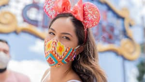 Woman with mickey ears and multi colored face covering looks at camera in Disney's Magic Kingdom park.