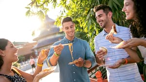 Four friends try snacks together in Epcot's World Showcase.