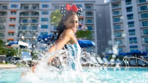 A young woman wearing a Minnie Mouse earband while splashing in a swimming pool at Disney's Riviera Resort