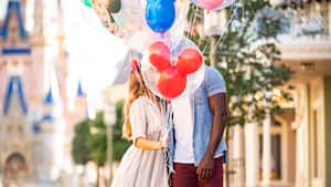 Man and woman stand in the middle of Main Street USA with colorful Mickey balloons in front of their faces