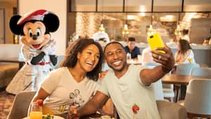 Man and woman have breakfast at Topolino and take a selfie with Minnie distant in the background