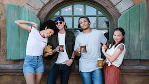 4 young adults enjoying coffee together at Magic Kingdom park