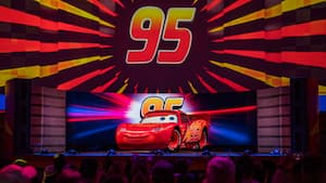 Lightning McQueen, onstage, with his racing number featured above him