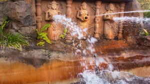 A rock wall with carvings and water spouts at Disney's Animal Kingdom