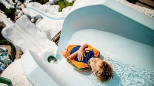 Un joven cierra los ojos y se prepara para deslizarse por Summit Plummet en el Parque Acuático Disney's Blizzard Beach