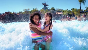Dos niñas abrazándose y sonriendo mientras una ola gigante las salpica en el Parque Acuático Disney's Typhoon Lagoon