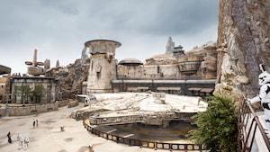 Um stormtrooper da Primeira Ordem olha para a Millennium Falcon pousada sob edificações exóticas de Star Wars e pináculos de madeira petrificados