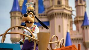 Goofy stands on a parade float with Cinderella Castle in the background