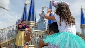 Una niña sentada sobre los hombros de su padre saluda a Snow White pasando en una carroza.