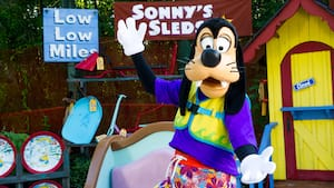 Goofy wears his bathing suit and a life vest as he stands in front of Sonny's Sleds