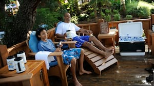 A father and son sit in lounge chairs drinking out of large mugs with a cooler of water bottles next to them