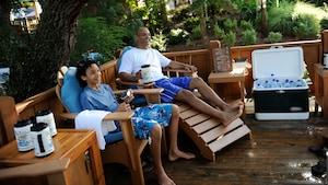 Un père et son fils sont assis sur des chaises longues et boivent dans de grandes tasses avec une glacière remplie de bouteilles d'eau à côté d'eux